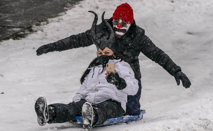 People ride on a sled amidst persistent snowfall on February 13, 2021 in Seattle, Washington. A large winter storm dropped heavy snow across the region. AFP