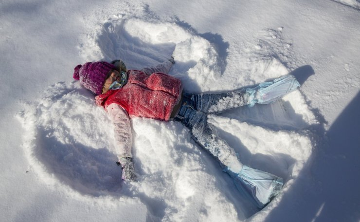 Annie Boon, 5, creates a snow angel while sledding with her family on Brookview Road in Austin, Texas, on Monday, Feb. 15, 2021. AP