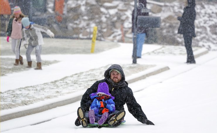 Andy German and Lyla, 6, sled down an icy street Monday, Feb. 15, 2021, in Nolensville, Tenn. Much of Tennessee was hit with a winter storm that brought freezing rain, snow, sleet and freezing temperatures. AP