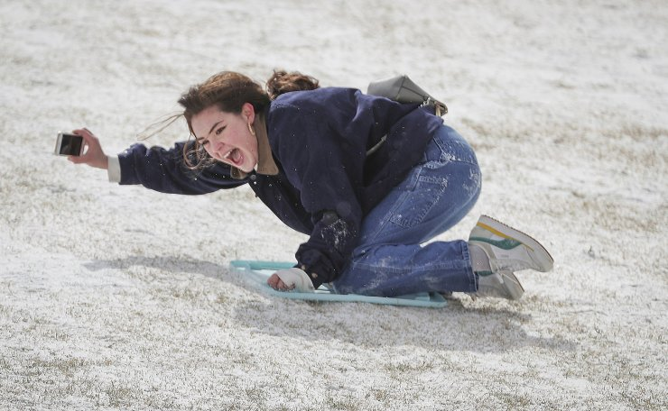 Rice University students Belen Szentes documents her sled ride on the Miller Outdoor Theatre hill Monday, Feb. 15, 2021, in Houston. A winter storm making its way from the southern Plains to the Northeast is affecting air travel. AP