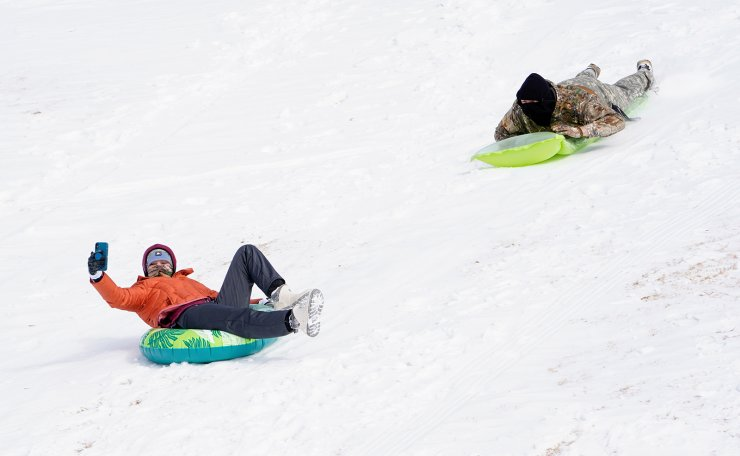 Alyssa Kocon, left, and Sam Sharp, right, sled down a hill using pool floats during record breaking cold weather in Oklahoma City, Oklahoma, U.S., February 15, 2021. REUTERS
