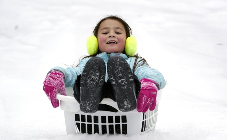 Peyton McKinney uses a laundry basket for a sled Monday, Feb. 15, 2021, in Nolensville, Tenn. Much of Tennessee was hit with a winter storm that brought freezing rain, snow, sleet and freezing temperatures. AP