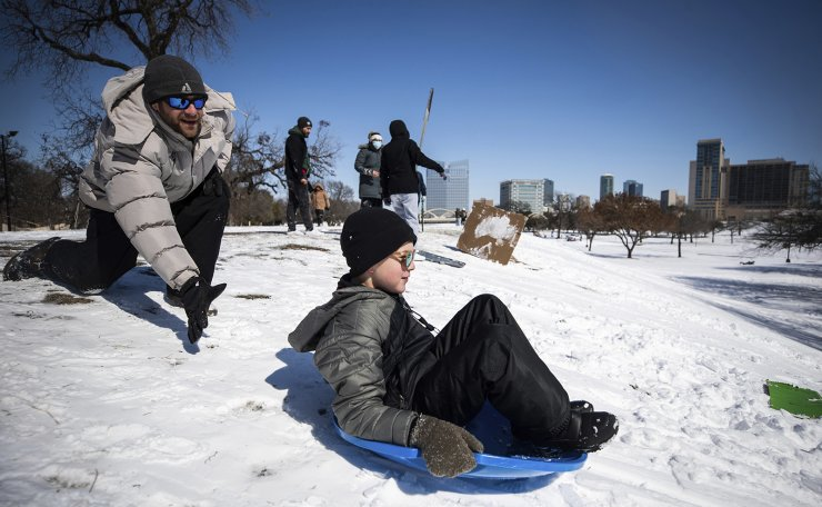 Matthew Etherington says after he gives Fin Etherington, 9, a push as he sleds down the hill Monday, Sept. 15, 2021, at Trinity Park in Fort Worth, Texas. A frigid blast of winter weather across the U.S.  has left more than 2 million people in Texas without power. AP