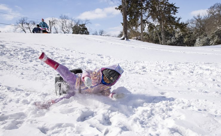 Mia Donjuan, 4, falls off her sled as she slides down a hill in the Elmwood neighborhood of Dallas on Monday, Feb. 15, 2021. AP