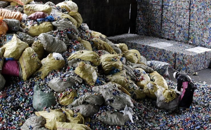 A worker sorts cans from household waste following the Lunar New Year's holiday, at a resource recycling facility in Seoul, South Korea, Tuesday, Feb. 16, 2021. AP