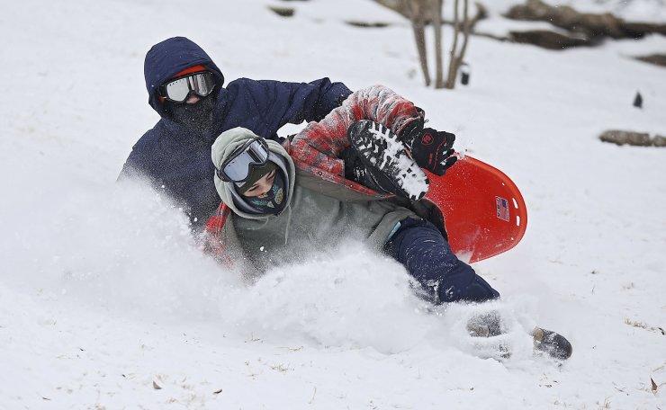 Ben Marsh, left, and Spencer Rittenberg tip over while sledding in the snow at Harwelden Mansion Monday, Feb. 15, 2021, in Tulsa, Okla. AP