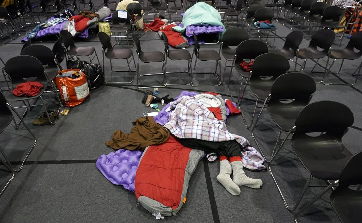 People seeking shelter from below freezing temperatures rest inside a church warming center Tuesday, Feb. 16, 2021, in Houston. More than 4 million people in Texas still had no power a full day after historic snowfall and single-digit temperatures created a surge of demand for electricity to warm up homes unaccustomed to such extreme lows, buckling the state's power grid and causing widespread blackouts. AP