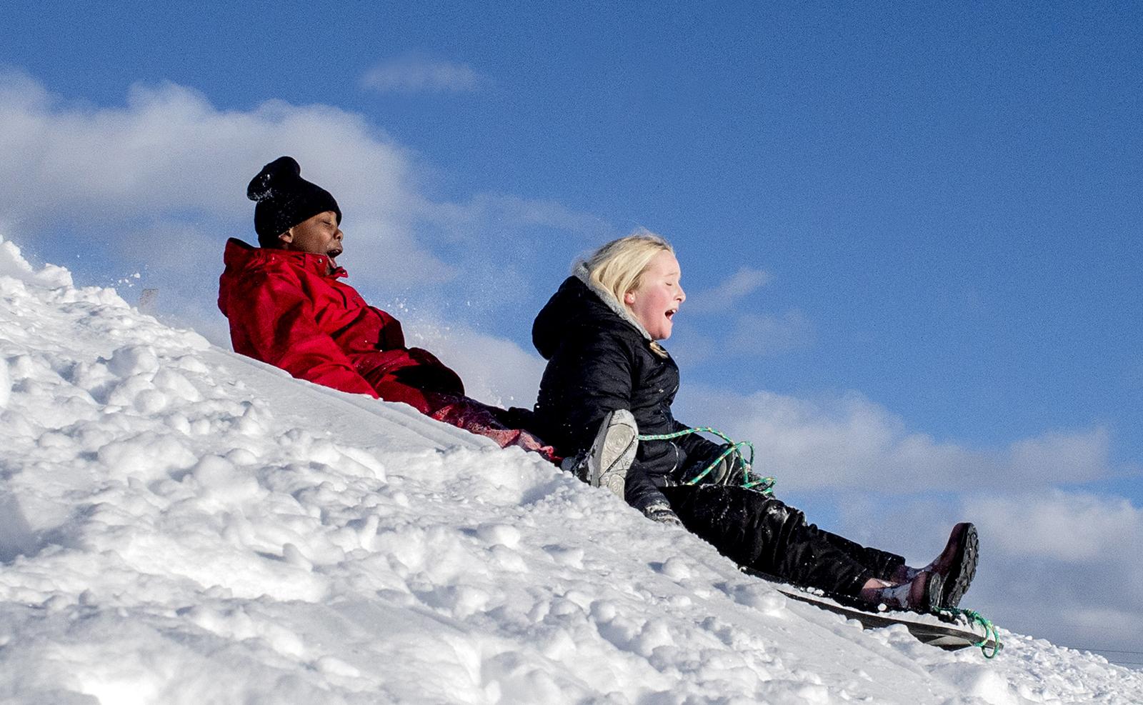 Matt Gerber Jr., 9, left, of Flint, Mich., and Addisen Athey, 11 of Swartz Creek, Mich., sled downhill Tuesday, Feb. 16, 2021, at Southwestern Classical Academy in Flint, after an overnight snowfall. AP
