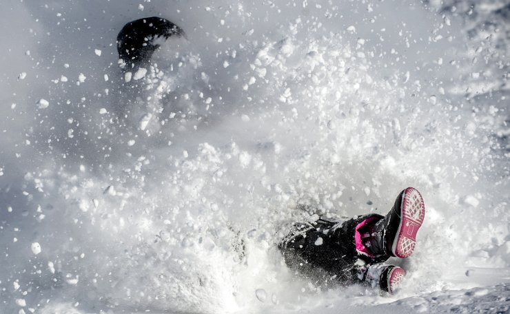 A cascade of snow pummels Flint, Mich., resident Aliesha Gilmore, left, and her 7-year-old daughter Mackenzie Metevier while the duo sleds at Southwestern Classical Academy Tuesday, Feb. 16, 2021, in Flint, Mich., after more than 9 inches of snow fell overnight. AP