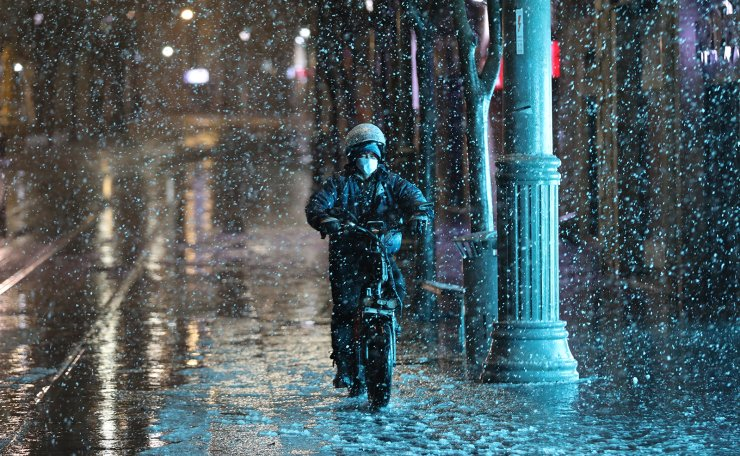 A man ride bicycle as snow falls in a main street in Jerusalem, 17 February 2021. Israeli Forecasters and the Meteorological Service expect snow fall in Jerusalem.  EPA