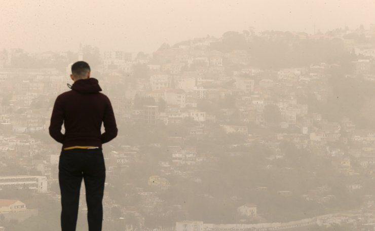 A man watches a cloud of sand dust coming from the Sahara desert flying over Algiers, Sunday, Feb.21, 2021. Recently, the Saharan dust plume, which covers parts of Southern and Central Europe, has caused short, rapid spikes in air pollution throughout the region. AP