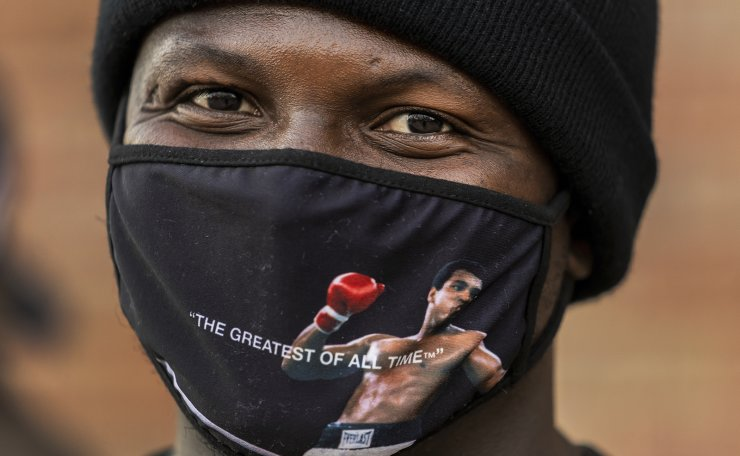 Photographer Michael Omeka wears a face mask with a Muhammad Ali image as he participates in the rally 'Love Our Communities: Build Collective Power' to raise awareness of anti-Asian violence outside the Japanese American National Museum in Little Tokyo in Los Angeles Saturday, March 13, 2021. AP