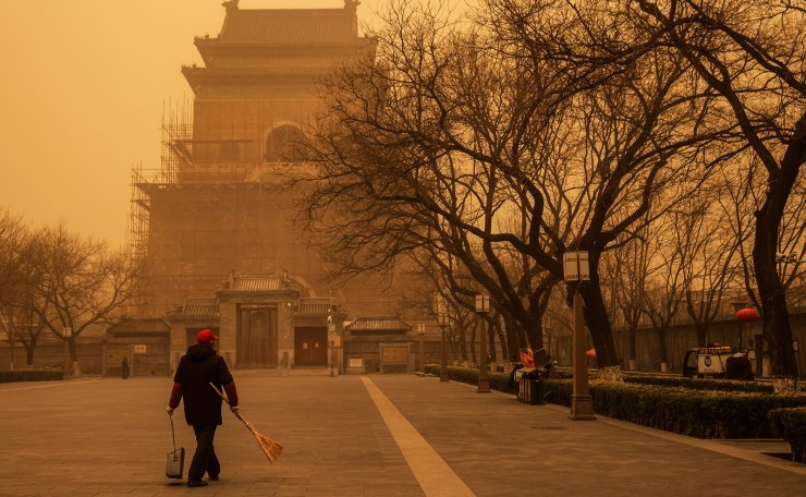 A person walks with a broom and dustpan during morning rush hour as Beijing, China, is hit by a sandstorm, March 15, 2021. Reuters
