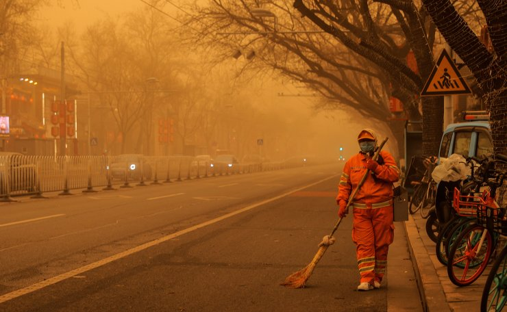 A sweeper walks with a broom along a road during morning rush hour as Beijing, China, is hit by a sandstorm, March 15, 2021. Reuters