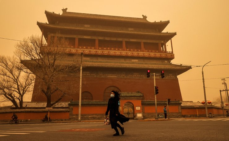 A woman walks past Drum Tower during morning rush hour as Beijing, China, is hit by a sandstorm, March 15, 2021. Reuters