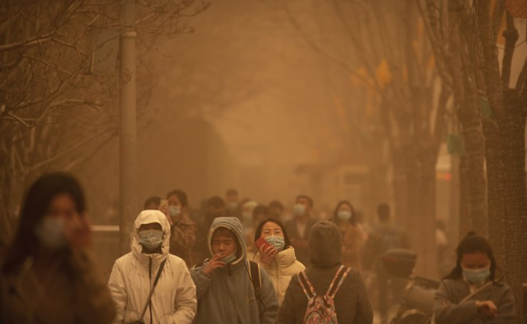 Commuters walk along a sidewalk amid a sandstorm during the morning rush hour in the central business district in Beijing, Monday, March 15, 2021. AP