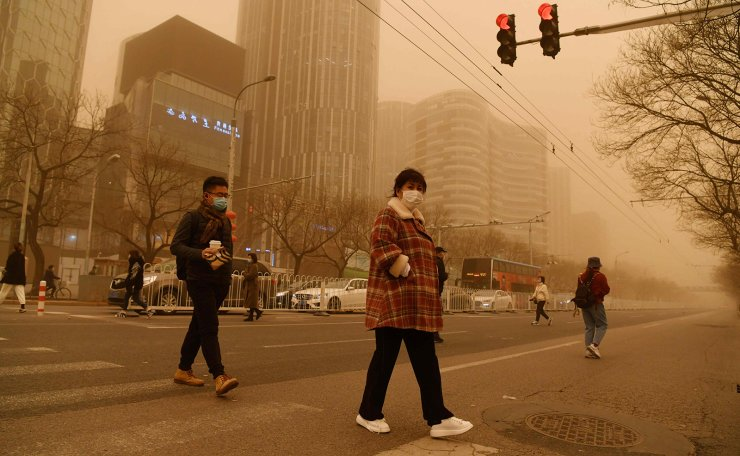 People cross a road during a sandstorm in Beijing on March 15, 2021. AFP