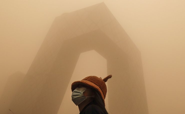 A woman wearing a face mask to help curb the spread of the coronavirus stands against the China Central Television (CCTV) building as capital city is hit by polluted air and a sandstorm in Beijing, Monday, March 15, 2021. AP