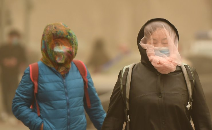 People wearing face masks and veils walk in dust in Beijing, capital of China, March 15, 2021. Floating dust hit Beijing on Monday. Xinhua