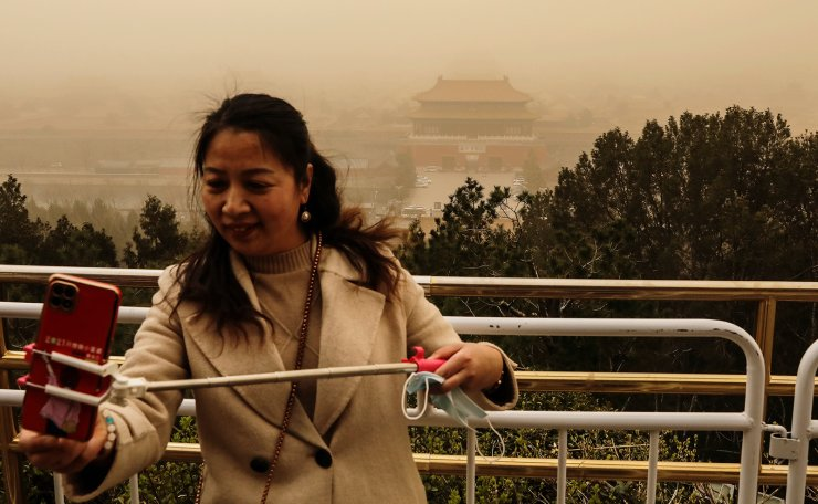 A visitor uses her smartphone on a selfie stick at a peak overlooking the Forbidden City at Jingshan Park, while the city is hit by a sandstorm, in Beijing, China March 15, 2021. Reuters