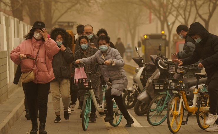 Residents make their way through a sandstorm in Beijing, Monday, March 15, 2021. The sandstorm brought a tinted haze to Beijing's skies and sent air quality indices soaring on Monday. AP