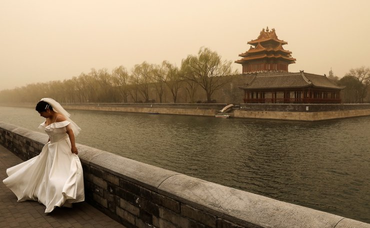 A woman in bridal gown adjusts herself during a wedding photoshoot near the Forbidden City, as the city is hit by sandstorm, in Beijing, China March 15, 2021. Reuters