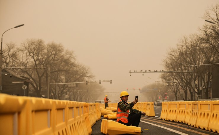 A road worker uses his smartphone in Beijing, China, as the city is shrouded in haze after a sandstorm, March 15, 2021. Reuters