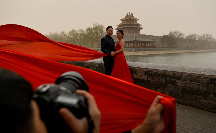 A couple poses for wedding photographs outside the Forbidden City during a sandstorm in Beijing on March 15, 2021. AFP
