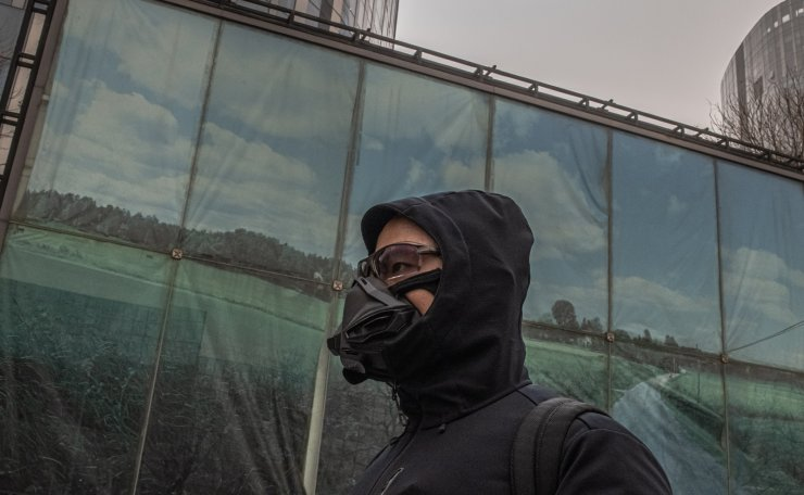 A man wearing a protective face mask walks in the shopping and residential area of Sanlitun on a heavy sandstorm day, in Beijing, China, 15 March 2021. EPA