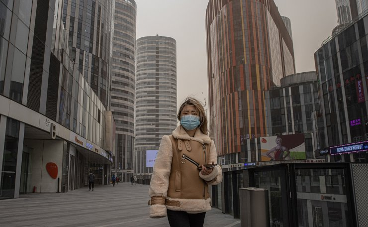 A woman wearing a protective face mask walks in the shopping and residential area of Sanlitun on a heavy sandstorm day, in Beijing, China, 15 March 2021. EPA