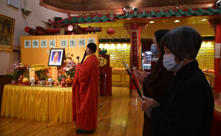 Worshippers offer prayers for victims of the Atlanta spa shooting in addition to the ongoing Covid-19 pandemic at the Mahayana Buddhist temple in Chinatown, New York City on March 17, 2021. AFP
