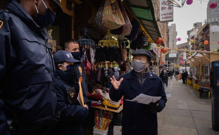 A resident speaks to police officers handing out information advising how to report hate crimes, in Chinatown, New York City on March 17, 2021, following the shootings in Atlanta. AFP