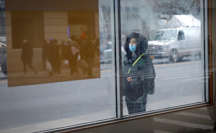 An Asian woman stands outside a closed storefront in the Chinatown section of Manhattan following the deadly shootings at three spas in Georgia, in New York City, New York, U.S., March 17, 2021. REUTERS