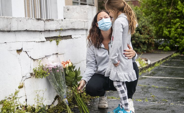 Mallory Rahman and her daughter Zara place flowers near a makeshift memorial outside of the Gold Spa in Atlanta, Wednesday, March 17, 2021. AP