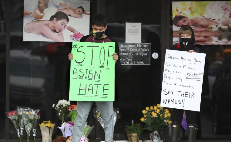 After dropping off flowers Jesus Estrella, left, and Shelby S., right, stand in support of the Asian and Hispanic community outside Youngs Asian Massage parlor where four people were killed, Wednesday, March 17, 2021, in Acworth, Ga. AP