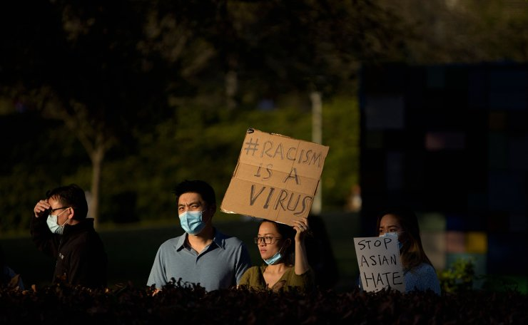A woman holds up a sign during a Stop Asian Hate rally at Discovery Green in downtown Houston, Texas on March 20, 2021. AFP