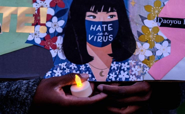 A woman holding a candle and an anti-hate sign takes part in a candlelight vigil in standing up against Asian American Pacific Islander (AAPI) hate and violence, at Almansor Park in Alhambra, California, on March 20, 2021. AFP