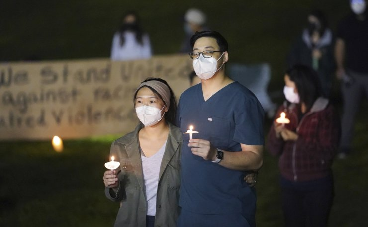 Hundreds of people gather at a candlelight vigil called 'Stop Asian Hate' at Almansor Park in Alhambra, Calif., Saturday night, March 20, 2021. AP