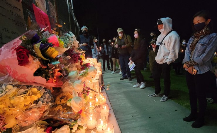 People pay their respects at an altar with flowers and candles at a candlelight vigil called 'Stop Asian Hate' at Almansor Park in Alhambra, Calif., Saturday night, March 20, 2021. AP