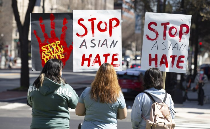 People with signs join hundreds of people gathering at a rally to voice opposition toward hatred against Asians, at McPherson Square in Washington, DC, USA, 21 March 2021. EPA
