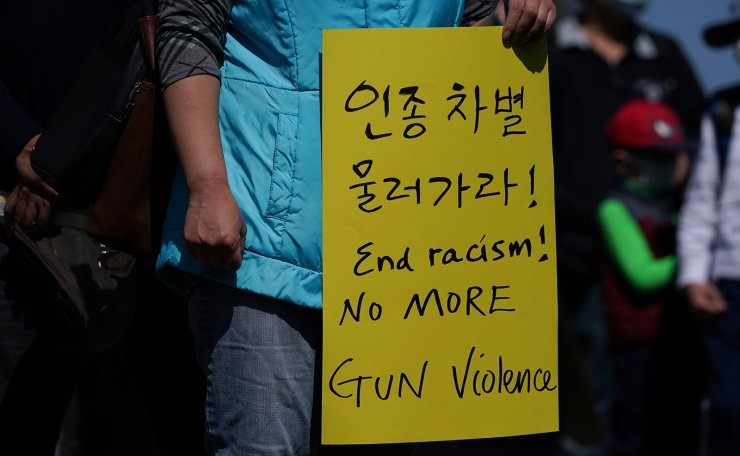 A person holds a sign as people rally to protest recent violence against people of Asian decent at McPherson Square near the White House in Washington, U.S. March 21, 2021. REUTERS