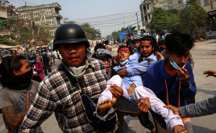 People carry an injured demonstrator during a protest against the military coup in Mandalay, Myanmar, 22 March 2021. EPA