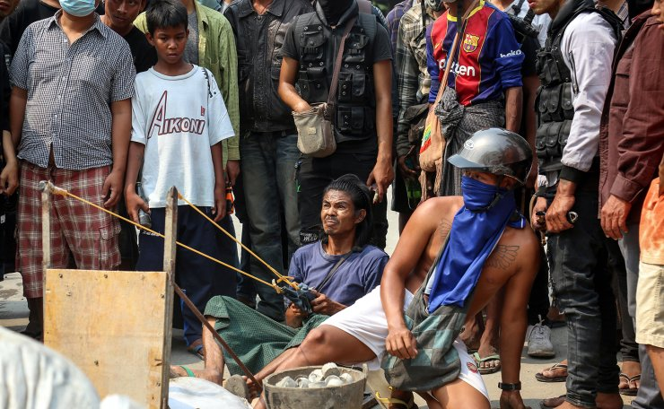 Demonstrators use a slingshot during a protest against the military coup in Mandalay, Myanmar, 22 March 2021. Anti-coup protests continued despite the intensifying violent crackdowns on demonstrators by security forces. EPA
