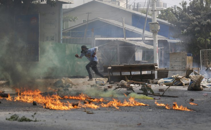 A man runs past a road barricade and burning debris Monday, March 22, 2021, in Mandalay, Myanmar. AP