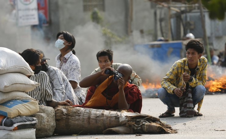 A Buddhist monk uses binoculars while with other men squatting behind a road barricade Monday, March 22, 2021, in Mandalay, Myanmar. AP