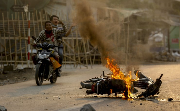 Two men on a motorbike alert people and anti coup protesters as armed security forces arrive to crack down on a demonstration in Mandalay, Myanmar, Tuesday, March 23, 2021. AP