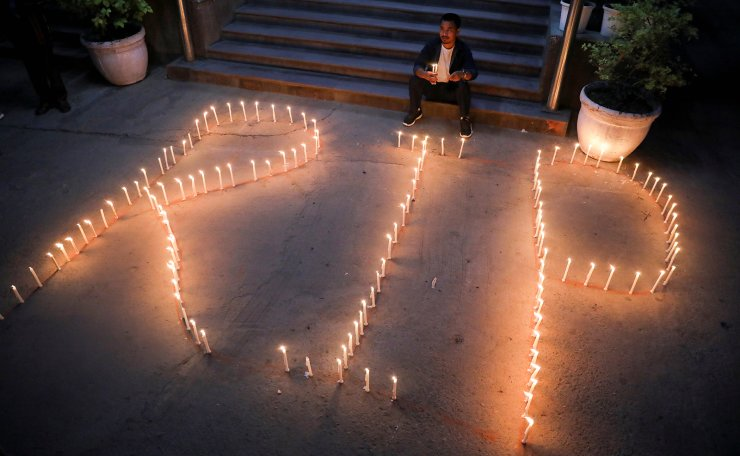 A person sits on the stairs during a candle vigil organized by Myanmar citizens living in India and members of Mizo Zirlai Pawl (MZP), a student organisation from India's Mizoram state, to pay tribute to people who died in Myanmar after the military coup, in New Delhi, India, March 23, 2021. REUTERS