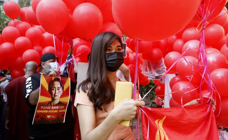 Protesters hold placards and a flag of the National League for Democracy (NLD) party attached to red balloons during a protest against the military coup, in Yangon, Myanmar, 24 March 2021. Anti-coup protests continue despite the intensifying violent crackdowns on demonstrators by security forces. EPA