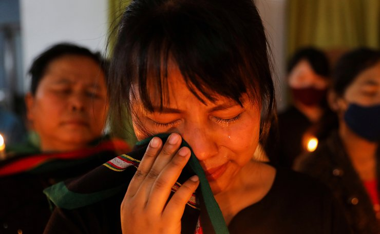 A woman reacts during a candle vigil organised by Chin Refugee Committee, to pay tribute to people who died in Myanmar after the military coup, in New Delhi, India, March 24, 2021. REUTERS