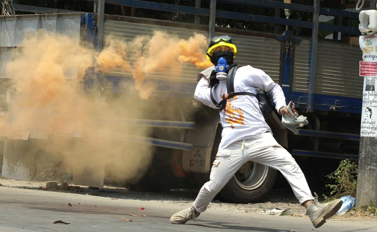 An anti-coup protester throws a smoke bomb against police crackdown in Thaketa township Yangon, Myanmar, Saturday, March 27, 2021. AP